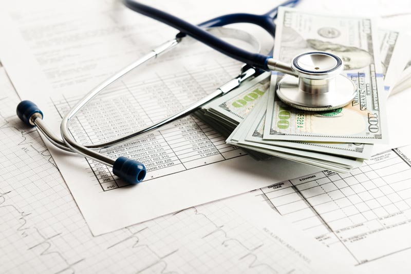 stack on money on medical charts with a stethoscope
