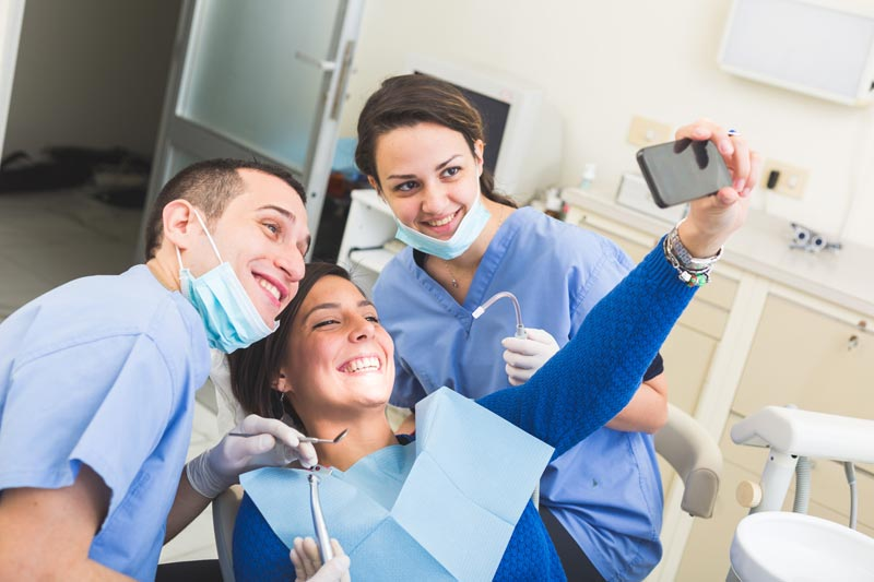 Dental patient takes a selfie with the dentist and dental hygienist.