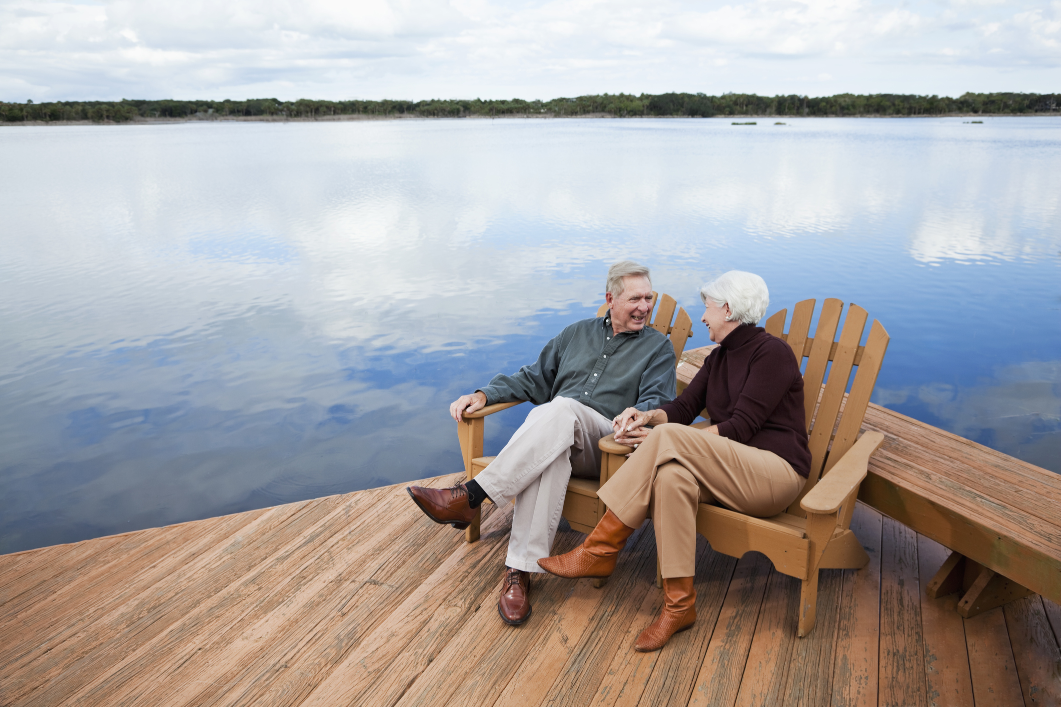 retired couple sits on lake deck