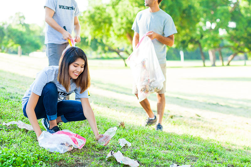 young woman helps pick up trash as a random act of kindess