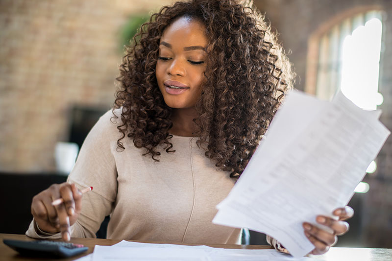 woman reviews her bank statements in order to complete an audit of her budget