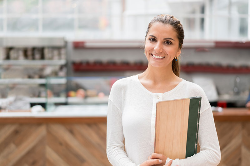 young woman holds menus at the restaurant she works at while she's on a work holiday visa