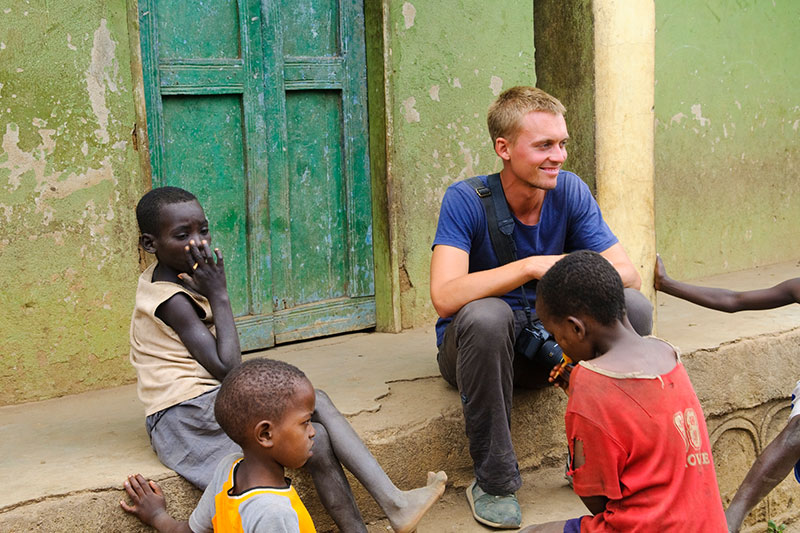 Young man sits with African children in a village where he is volunteering
