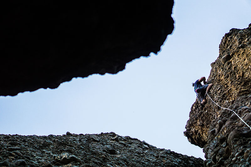 looking up through the rocks at a rock climber