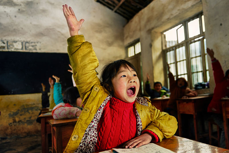 young Asain girl raises her hand in a classroom